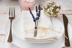Romantisches Gedeck, Hochzeit, Lavendel, weiße kleine Blumen, Platten, Serviette, brennende Kerze, hölzerne Tabelle, draußen Lizenzfreie Stockfotos