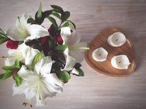 Romantisches Gedeck mit Blumen und Kerzen auf dem weißen Holztisch Stockbilder