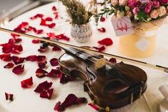 Romantisches Gedeck mit schönen Blumen im Kasten, stieg Blumenblätter und Violine lizenzfreie stockfotografie