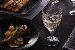 Romantisches gesundes Abendessen mit Lachsen und Weißwein auf Schwarzem Lizenzfreie Stockfotos