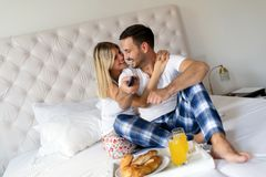 Romantisches glückliches Paar, das im Bett frühstückt Lizenzfreie Stockfotografie