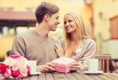 Romantisches glückliches Paar mit Geschenk im Café Lizenzfreie Stockbilder
