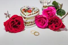 Romantisches Herz formte künstlerisches Schmuckkästchen mit hellen roten und rosa Rosen mit Goldverlobungsringen auf hellem Hinte Stockbild