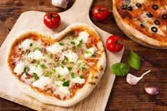 Romantisches Herz-geformte italienische Pizza Margherita Stockbilder