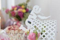 Romantisches Liebeszeichen auf einem Käfig mit Taube und Blumen auf Hintergrund Lizenzfreie Stockbilder