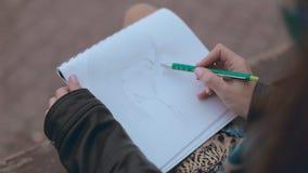 Romantisches Mädchen, das auf einer Bank und einem zeichnenden Paar sitzt stock footage