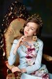 Romantisches Mädchen in der Krone von schönen Ohrringen und herein von sitzen Lizenzfreies Stockfoto