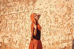 Romantisches Mädchen in der roten Kleidung träumend an der Wand mit Zeichen von modernen Graffiti auf der Wand des Hauses Lizenzfreies Stockfoto
