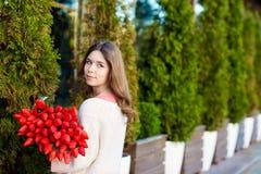 Romantisches Mädchen mit einem Blumenstrauß von roten Tulpen stockfotos