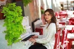 Romantisches Mädchen, das auf einem alten Klavier im Straßencafé spielt Stockfotografie