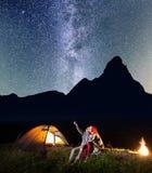 Romantisches Paar sitzt nahe dem glühenden Zelt und dem Lagerfeuer und schaut zu den Sternen im nächtlichen Himmel Stockfotografie