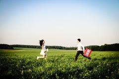 Romantisches Paar von Liebhabern auf dem Gebiet läuft in Richtung zu einander Lizenzfreies Stockbild