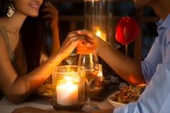 Romantisches Paarhändchenhalten zusammen über Kerzenlicht stockbilder