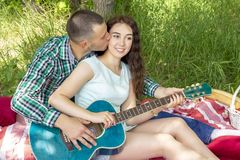 Romantisches Picknick des Sommers Kerl zeigt dem Mädchen, wie man die Gitarre spielt Paare, die auf dem Gras sitzen stockfotografie