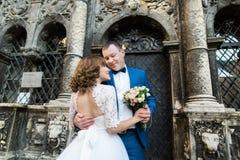 Romantisches Porträt im Freien der lächelnden umarmenden Jungvermählten beim Halten des Heiratsblumenstraußes lizenzfreie stockfotos