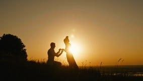 Romantisches Schattenbild des Mannes erhalten unten auf seinem Knie und zur Frau auf hohem Hügel vorschlagend - Paar verlobt sich stock video footage