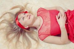 Romantisches süßes reizend blondes Mädchen im roten Kleid und Band auf ihrem Haupt, Spaß habend, entspannen herein sich liegendes Stockfoto