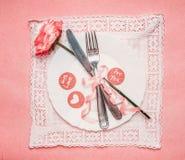 Romantisches Tabellengedeck mit Platte, stieg, Tischbesteck und Band auf rosa blassem Hintergrund Lizenzfreie Stockfotografie