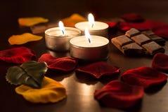 3 romantisches Tealights mit Schokolade und Rose Petals Stockfoto
