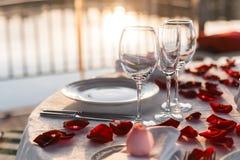 Romantisches Valentinstagabendessen gegründet mit den rosafarbenen Blumenblättern stockfoto