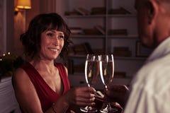 Romantisk afton av lyckliga höga par med lo för champagneflöjter Arkivbilder