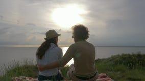 Romantisk avkoppling, vänner grabb och flicka som vilar på grön äng nära floden med skinande vatten på solnedgång i himmel lager videofilmer