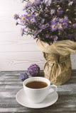 Romantisk bakgrund med en kopp te, lila blommar i en vas på en grå trätabell fotografering för bildbyråer