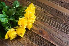 Romantisk bakgrund med gula rosor som ligger på en trätabell Arkivfoto