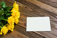Romantisk bakgrund med gula rosor som ligger på en trätabell Royaltyfri Fotografi