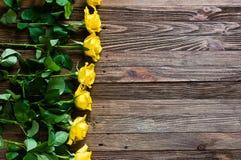 Romantisk bakgrund med gula rosor som ligger på en trätabell Royaltyfri Foto