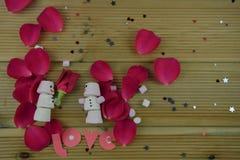 Romantisk bild för vintersäsongfotografi med marshmallower som formas som snögubben med med is leenden på och rymma en röd rosblo fotografering för bildbyråer