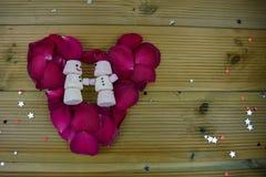Romantisk bild för vintersäsongfotografi med röda rosor i en hjärtaform och marshmallower som formas som den lyckliga snögubben p Fotografering för Bildbyråer