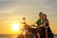 Romantisk bild med ett par av h?rliga stilfulla cyklister p? solnedg?ngen Den stiliga grabben med tatoo och den unga sexiga kvinn arkivbilder