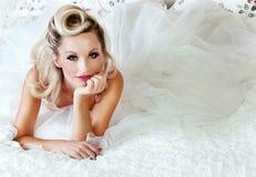 Romantisk blond kvinna som poserar i säng Arkivfoto