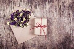 Romantisk bokstav med blommor Kuvert med blommor och en gåva Royaltyfria Foton