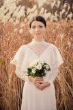 Romantisk brud med buketten i höstfältet Arkivfoto