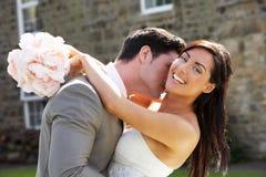 Romantisk brud och brudgum Embracing Outdoors royaltyfri bild