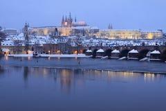 Romantisk färgrik snöig Prague för afton gotisk slott med Charles Bridge Arkivfoto