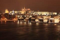 Romantisk färgrik snöig Prague för natt gotisk slott med Charles Bridge Arkivbild