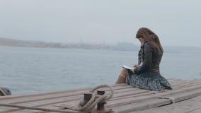 Romantisk flicka i kjolsammanträde på pir lager videofilmer