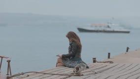 Romantisk flicka i kjolsammanträde på pir nära arkivfilmer