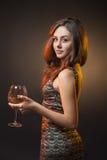 Romantisk flicka i klänning med exponeringsglas av vin Arkivfoton