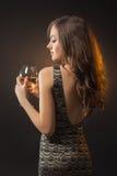 Romantisk flicka i klänning med exponeringsglas av vin Arkivfoto