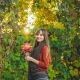Romantisk flickadet fria för skönhet som tycker om naturen som rymmer sidor i händer Härlig höstmodell med vinkande glödhår ljus  arkivbilder
