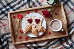 Romantisk frukost i säng för valentindag Rostade bröd med driftstopp, giffel, varm choklad, den röda rosblomman och kronblad arkivfoton