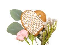 Romantisk gåva: Ingefära hjärta-formad kaka med isolerade blommor Royaltyfri Foto