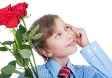 Romantisk gåvaidé. Härlig blond pojke som bär en skjorta och ett band som rymmer att le för röda rosor Royaltyfri Fotografi