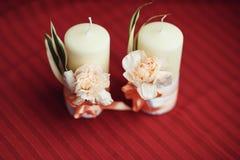 Romantisk garnering med två vita stearinljus Fotografering för Bildbyråer