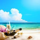 Romantisk havsstrand för konst. vinexponeringsglas och Champagne Bottle på san Arkivbilder