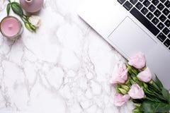 Romantisk kontorsbakgrund med blommor, stearinljuset och tangentbordet på en marmortabell royaltyfri fotografi